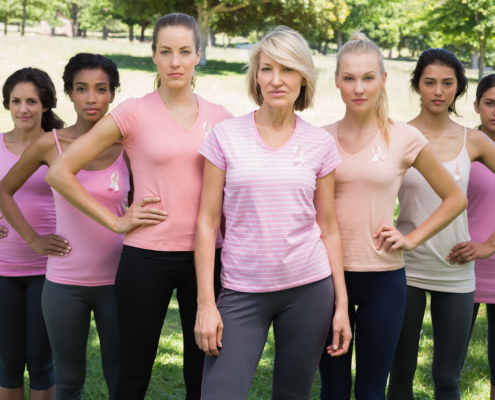 Portrait of confident women supporting breast cancer awareness at park